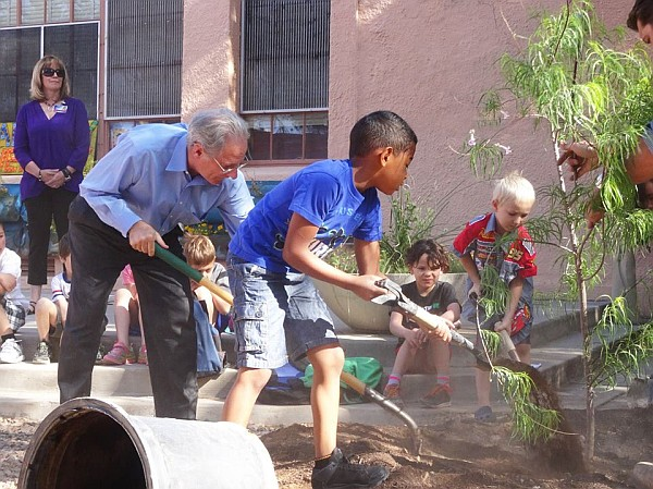 Mayor and a student with shovels, planting a tree
